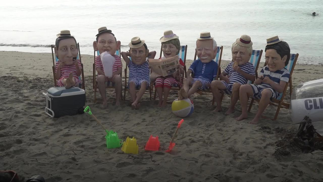 Oxfam campaigners stage protest posed as G7 leaders on beach