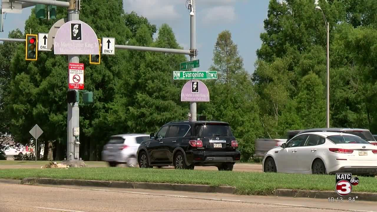Signs encouraging drivers to not give money to panhandlers, call hotline instead