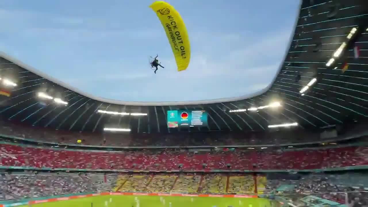 Fans react as Greenpeace parachutist skims their heads during Euro 2020 game