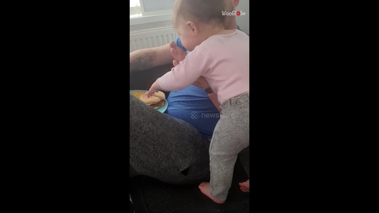 Baby is determined to get her hands on her dad's breakfast