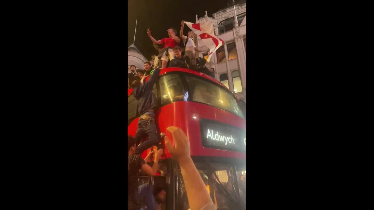 England fans dangerously climb on top of double-decker bus in central London