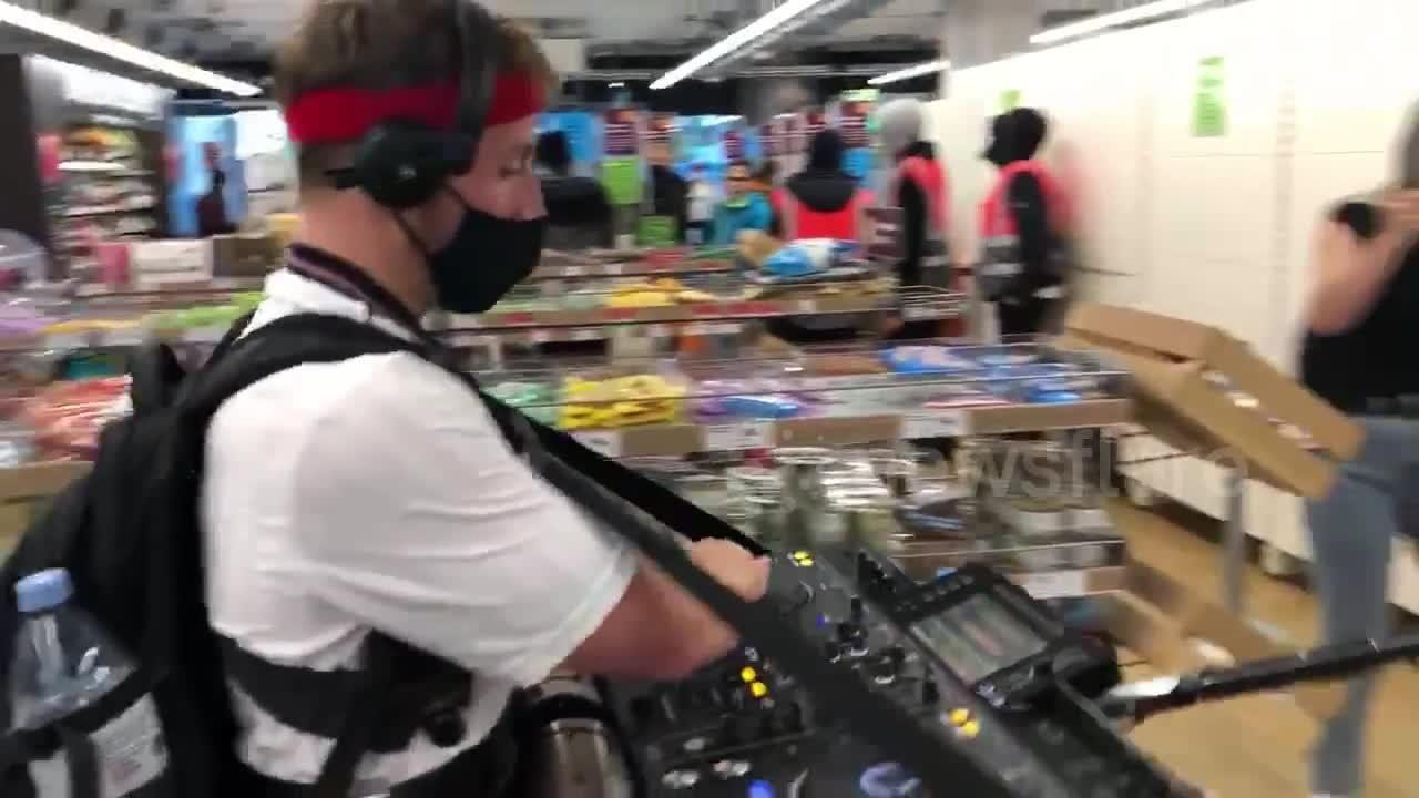 Mobile DJ in England shirt spins tunes as he wanders the aisles of a supermarket in Wembley
