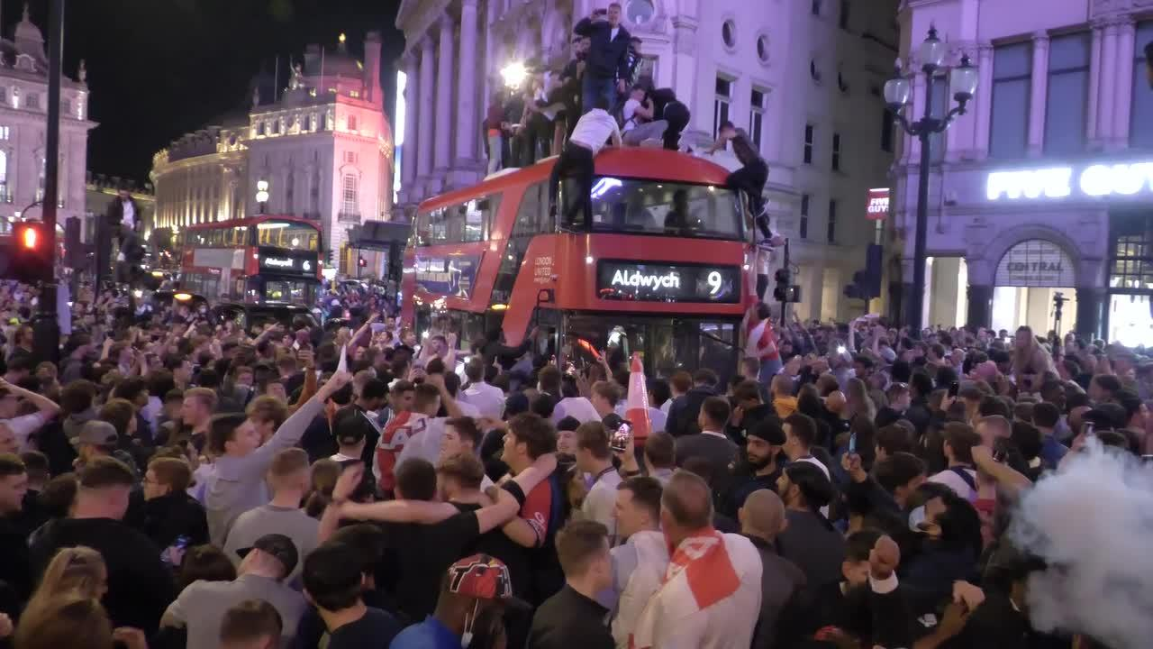 London ERUPTS with fans climbing on buses as England celebrate football win