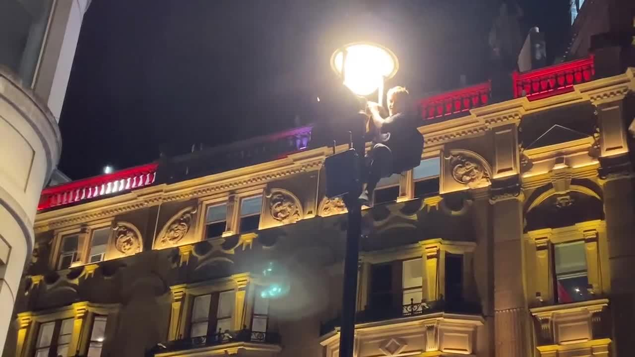 English supporters climb light poles in London following country's Euro 2020 win over Denmark