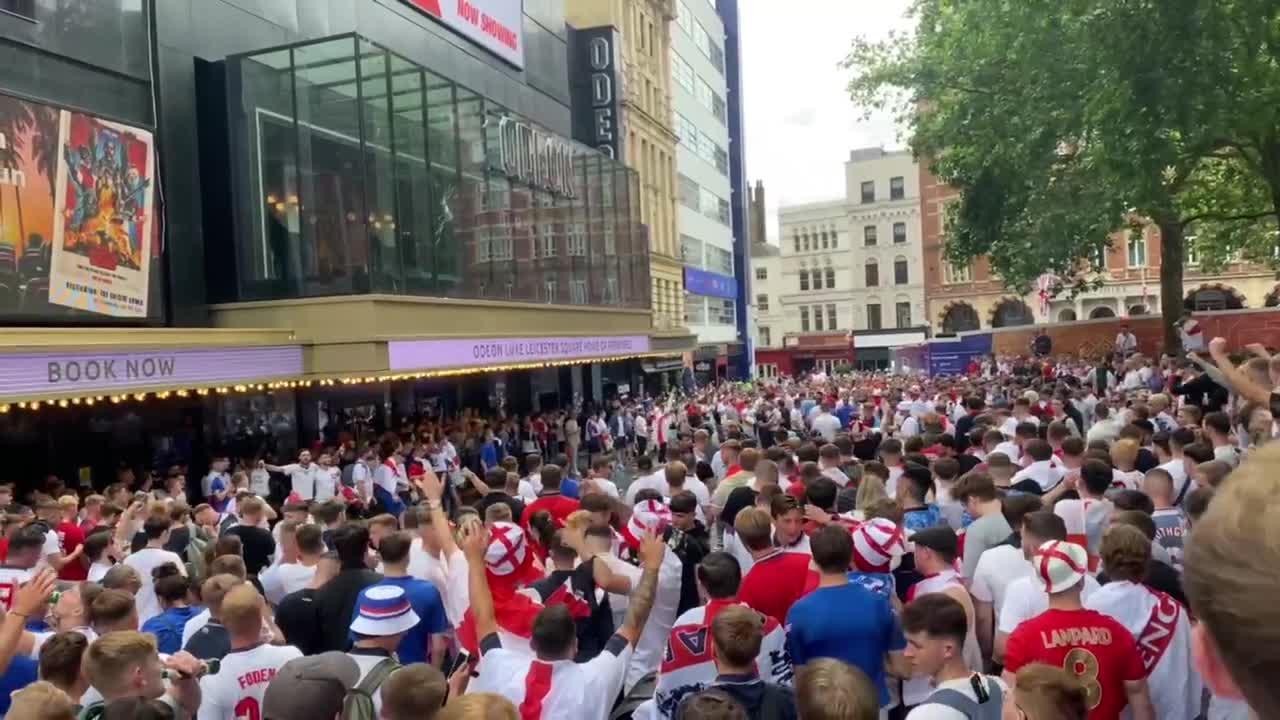 Huge England fan crowd in West End hurl bottles at fan standing on cinema roof