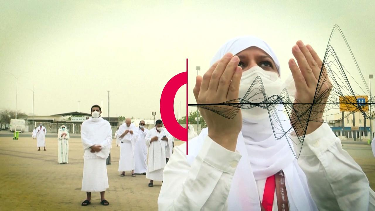 Pilgrims pray next to Mount Arafat